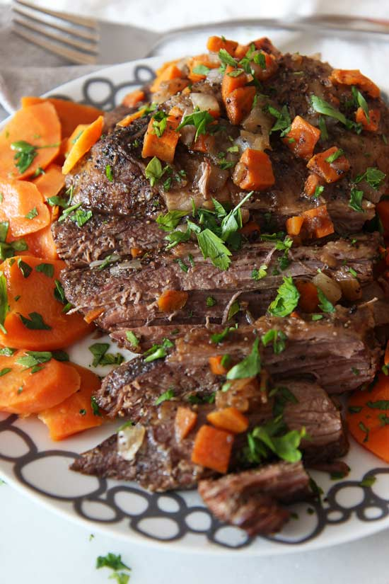 Slow Cooker Brisket Recipe - that is so easy and super comfort food tasty. Grab the meat, carrots, onions, onion soup mix, and all the wine you can pour. Happy #slowcooking. www.ChopHappy.com #dinner #holiday #Christmasrecipe #SundayDinner #Hanukkah