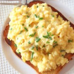How To Make The Creamiest Scrambled Eggs. This is a perfect simple brunch, breakfast, or dinner that has very little ingredients! Grab eggs, butter, sour cream, and chives. Happy Egg Cooking! www.ChopHappy.com #howtomakescrambledeggs #eggrecipe