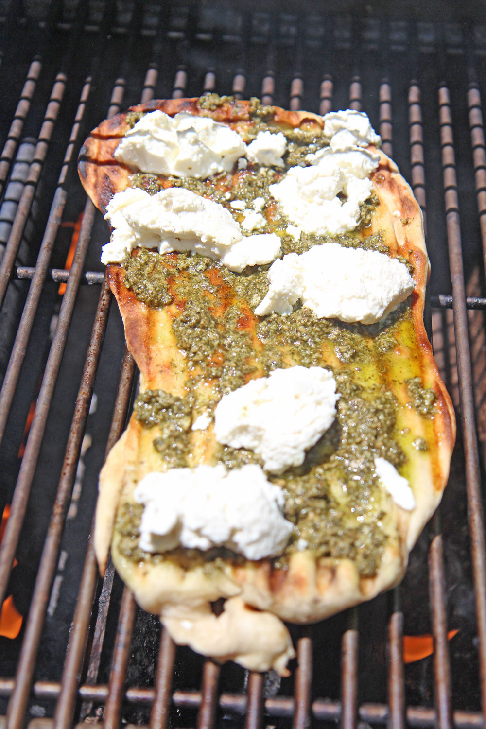 Easy Grilled Pesto Pizza Recipe. This is so easy to make. Grab pizza dough, pesto, riccota cheese, red pepper, and black pepper. You grill 2 minutes per side and dinner is ready. Happy grilling. www.ChopHappy.com #pizzarecipe #grillingrecipe