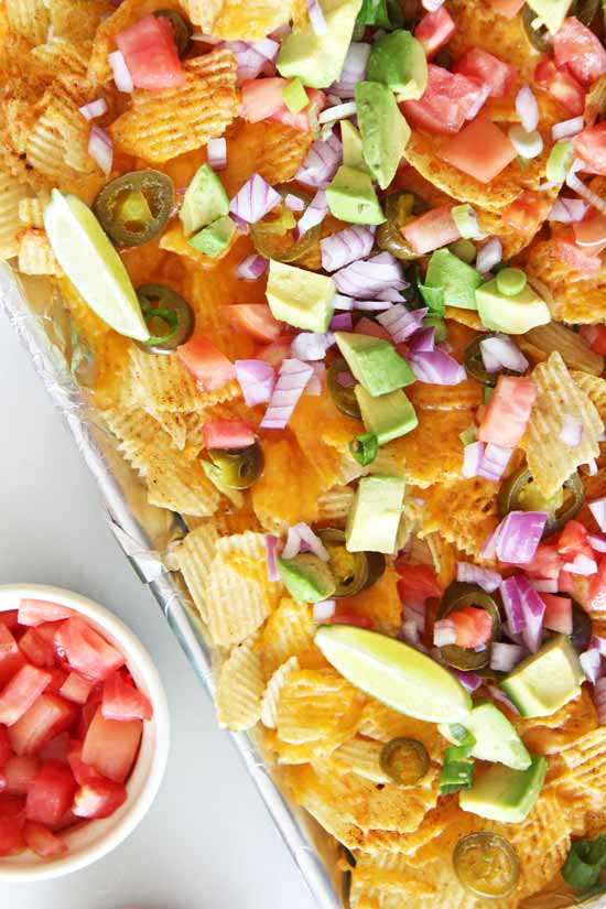 Potato Chip Nacho Recipe - is so fun everyone will smile when it hits the dinner table. Potato chips, seasoning, cheese, and bagged chips makes this easy. www.ChopHappy.com