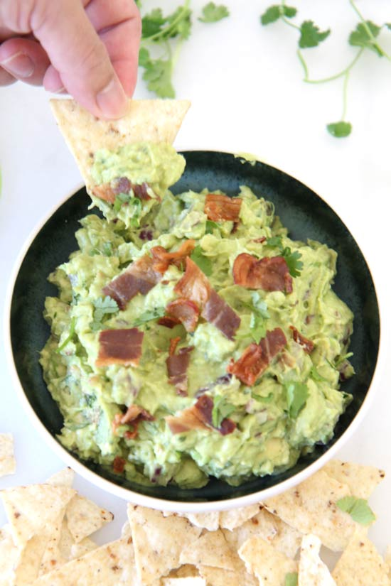 Bacon Guacamole Recipe - that is so creamy delicious you will not stop dipping. Grab avocados, vinegar, onion, and bacon. Happy appetizer making! www.ChopHappy.com