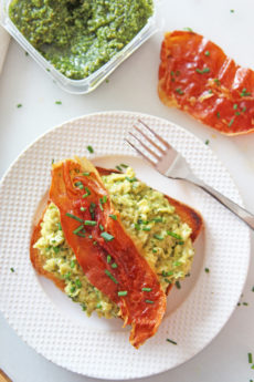 Green Eggs and Ham (Pesto Scrambled Eggs and Crispy Prosciutto) Recipe. Grab pesto, make the creamiest scrambles eggs, and grab a sheet pan for crispy sweet prosciutto. This is a fast treat yourself brunch, breakfast for dinner, or birthday recipe! Happy Cooking! www.ChopHappy.com #scrambled eggs #breakfastrecipe