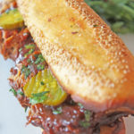 Huge BBQ Pork Sandwich with Garlic Bread Bun (slow cooker recipe). Grab pork ribs, BBQ sauce, pickles, and garlic bread. This is perfect party food, picnic, or summer time eats. Happy Cooking! www.ChopHappy.com #slowcookerecipes #sandwichrecipe