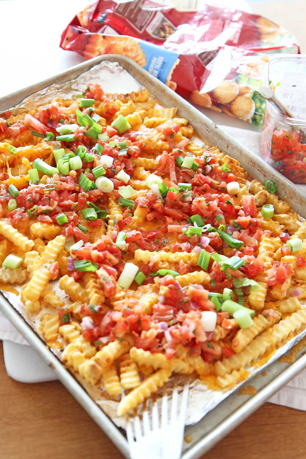 How to Transform Frozen Fries Into Loaded Taco Fries Recipe. Frozen fries, salsa, scallions, cheese, and chili seasoning. Transforming frozen fries is as easy as pantry seasonings cheese, and an oven. Happy sheet pan cooking! www.ChopHappy.com #frozenfries #tacos #pantry