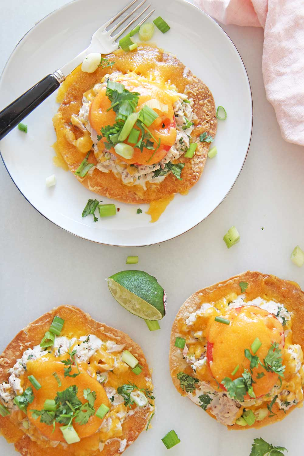 Tuna Melt Tostadas are so easy to make and are the perfect pantry dinner. Grab tortillas, tuna, mayo, cilantro, scallions, cheese, and lime. Happy Dinner cooking! www.ChopHappy.com #tostada #tunamelt