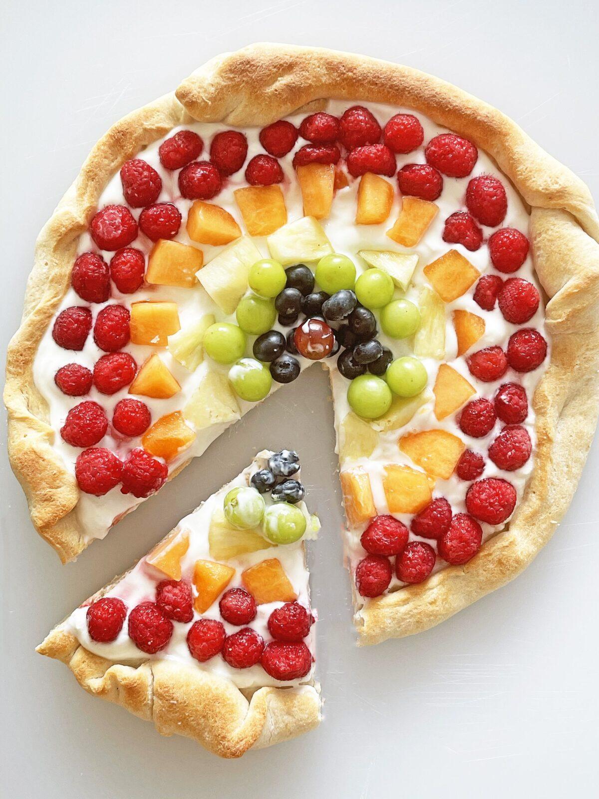 Rainbow Dessert Pizza Recipe. Super easy dessert pizza with just pizza dough, yogurt, and fruit. This is a fun dessert for everyone to make together. Happy Rainbow Pizza and Unicorn dessert dreams! #priderecipes #rainbowdessert